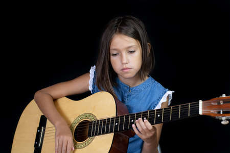 Small girl playing guitar on black background Imagens - 128789507
