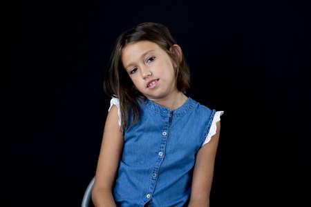 Little girl posing on black background Imagens