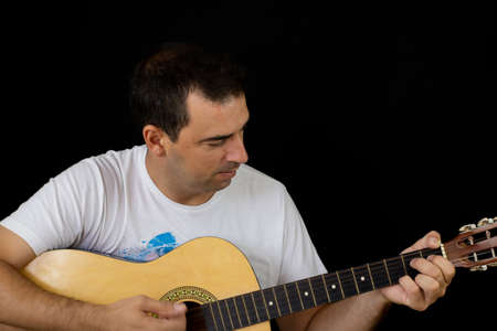 Man playing the guitar on black background Imagens - 128789911