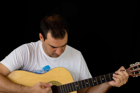Man playing the guitar on black background