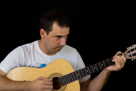 Man playing the guitar on black background Imagens - 128789982