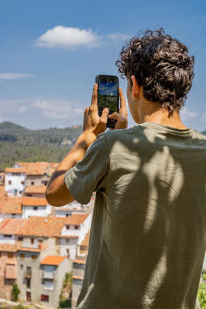 Young man photographing a mountain town Foto de archivo