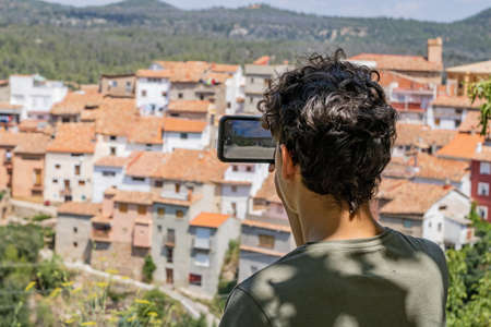 Young man photographing a mountain town Imagens - 128789987