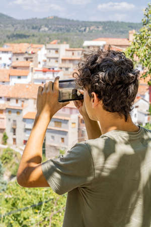 Young man photographing a mountain town Imagens - 128789990