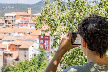 Young man photographing a mountain town Imagens