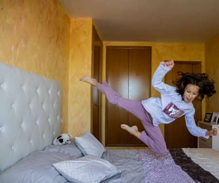 Little girl jumping in bed in pajamas Stockfoto