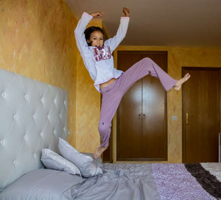 Little girl jumping in bed in pajamas Stockfoto - 133319919