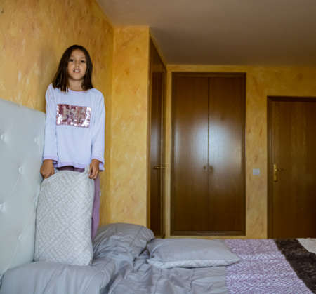 Little girl jumping in bed in pajamas Stockfoto - 133319922