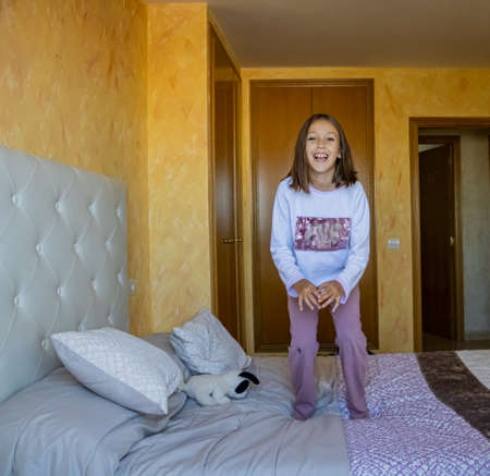 Little girl jumping in bed in pajamas Stockfoto - 133319799