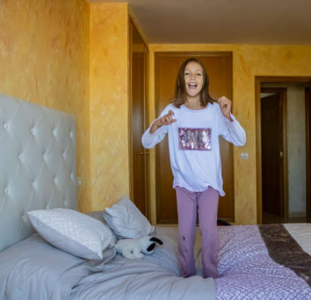 Little girl jumping in bed in pajamas Stockfoto - 133319803
