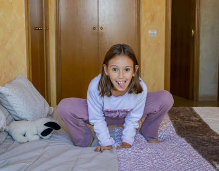 Little girl jumping in bed in pajamas Stockfoto - 133319806