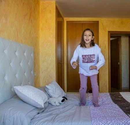 Little girl jumping in bed in pajamas Stockfoto - 133319696