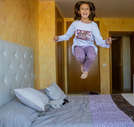 Little girl jumping in bed in pajamas Stockfoto - 133319698