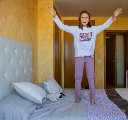 Little girl jumping in bed in pajamas Stockfoto - 133319700