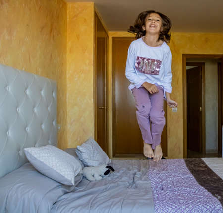 Little girl jumping in bed in pajamas Stockfoto - 133319703