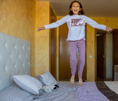 Little girl jumping in bed in pajamas Stockfoto - 133319704