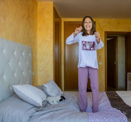 Little girl jumping in bed in pajamas Stockfoto - 133319705