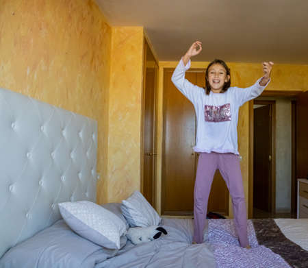 Little girl jumping in bed in pajamas Stockfoto - 133319654