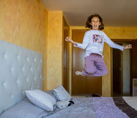 Little girl jumping in bed in pajamas Stockfoto - 133319655
