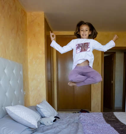 Little girl jumping in bed in pajamas Stockfoto - 133319666