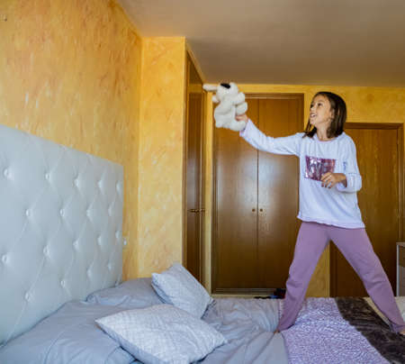 Little girl jumping in bed in pajamas Stockfoto - 133319680
