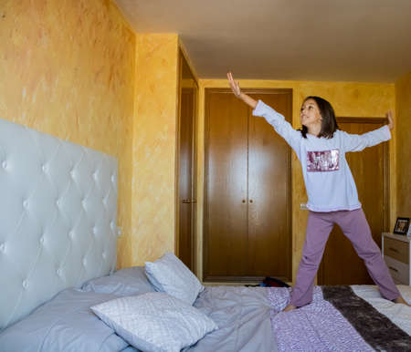 Little girl jumping in bed in pajamas Stockfoto - 133319683