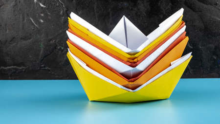 Origami paper boats stacked on blue and black background