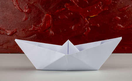 White origami paper boat on red background
