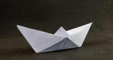 White origami paper boat on black background Imagens