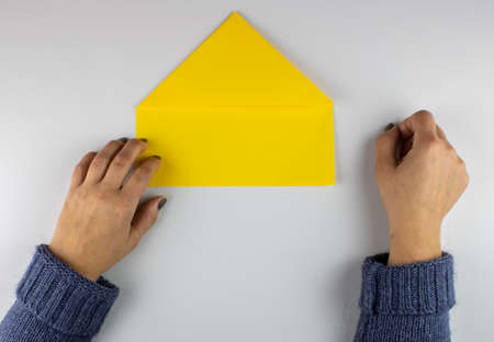 Woman folding a piece of paper on gray background Imagens