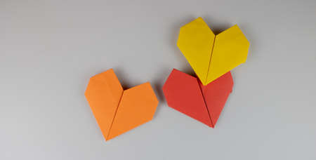 Origami hearts made of paper on gray background Imagens