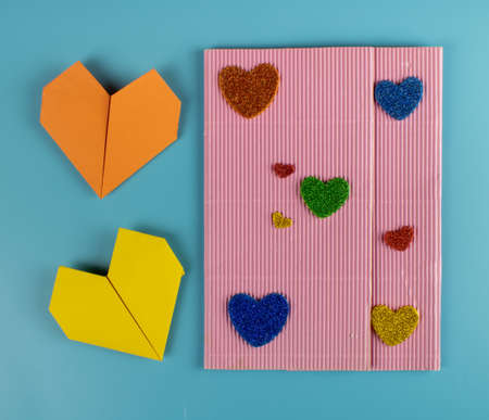 Origami hearts made of paper on blue background Imagens