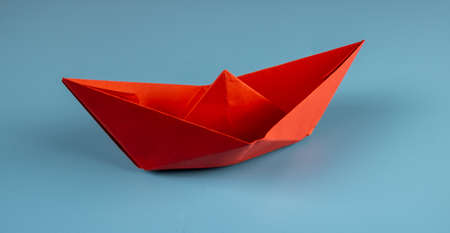 Red origami paper boat on blue background