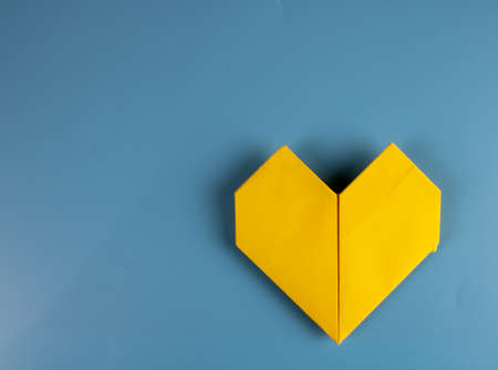 Origami heart made of paper on blue background