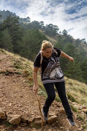 Woman doing hiking climbing to the peak of a mountain
