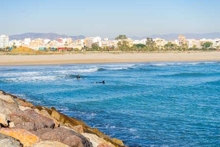 Men surfing in the Mediterranean Sea next to the breakwater Stockfoto - 138199579