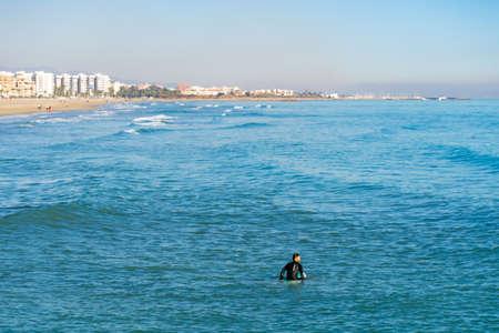 Men surfing in the Mediterranean Sea next to the breakwater