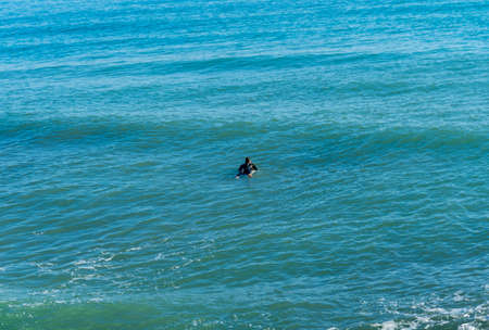 Man surfing in the Mediterranean Sea next to the breakwater