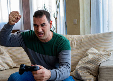 Angry man playing video games in the living room