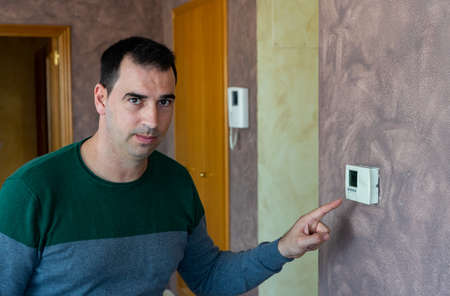 Man starting up the heating at home