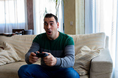 Amazed man playing video games in the living room Stockfoto