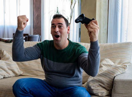 Happy man playing video games in the living room Stockfoto