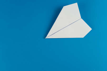 Handmade white paper plane on blue background in travel concept Stockfoto