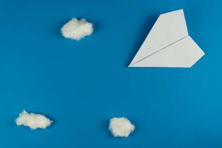 Handmade white paper plane on blue background with clouds made with cotton in travel concept