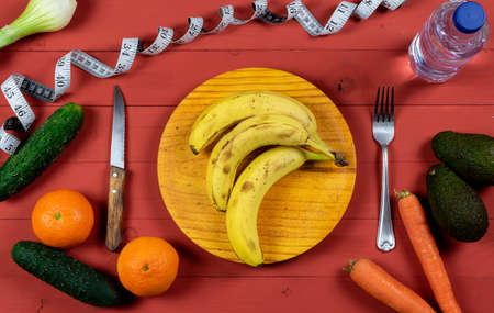 Bananas on wooden plate with avocados, oranges, carrots, scallions, cucumbers and a bottle of water on a red wooden table for diet concept