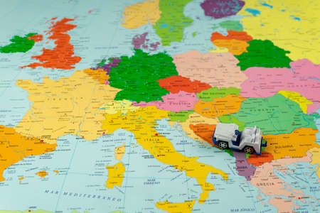 Small white and blue toy car on a colorful map of the continent in travel and adventure concept Stockfoto