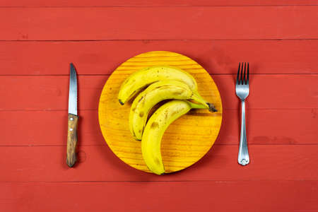 Ripe bananas on a wooden plate with cutlery on a red wooden table in concept of diet and healthy life Stockfoto