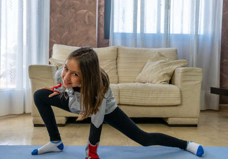 Little girl doing stretching in the living room at home on a blue mat