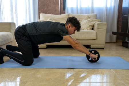 Young man with black sportswear practicing exercise in the living room at home on blue mat