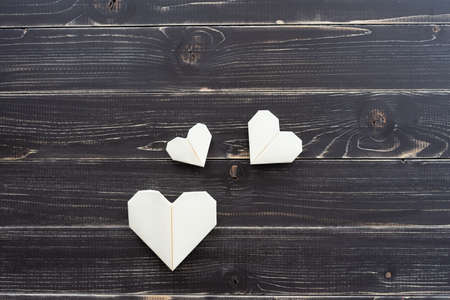 Origami hearts of different colors and sizes in composition on weathered black wooden background